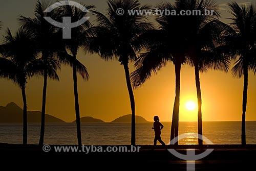 Assunto: Praia de Copacabana ao amanhecer com praticante de jogging e coqueiros. / Local: Copacabana - Rio de Janeiro - Rio de Janeiro (RJ) - Brasil / Data: 08 julho 2007