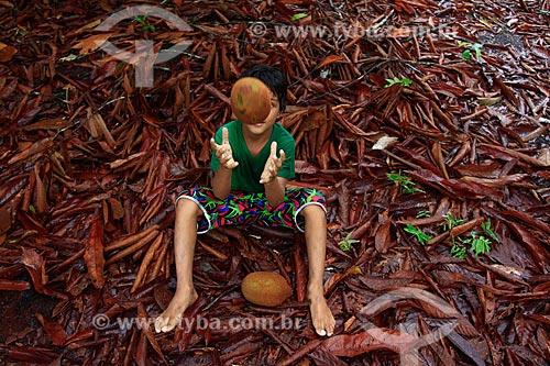 Assunto: Criança sentada brincando com cupuaçu / Local: Manaus - Amazonas (AM) - Brasil  / Data: 03/2011