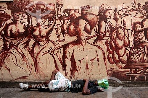 Assunto: Folião do carnaval dormindo no Arco do Teles, Travessa do Comércio, junto à mural retratando cena baiana / Local: Centro  -  Rio de Janeiro  -  Rio de Janeiro (RJ)  -  Brasil / Data: 02/2011