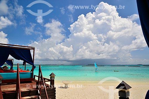 Assunto: Mulher deitada lendo com um windsurf no fundo / Local: Furanafushi - República das Maldivas - Ásia / Data: 04/2010