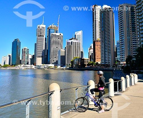 Assunto: Ciclista às margens do Rio Brisbane com edifícios ao fundo / Local: Brisbane - Queensland - Austrália - Oceania / Data: 07/2011