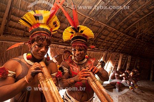 Índios Yawalapiti com tunacape (cocar) tocando a flauta Uruá no interior da maloca (oca) reservada aos homens denominada - Casa dos Homens, na aldeia Yawalapiti por ocasião do Kuarup - cerimônia deste ano em homenagem ao antropólogo Darcy Ribeiro - Imagem licenciada (Released 94) - ACRÉSCIMO DE 100% SOBRE O VALOR DE TABELA  - Gaúcha do Norte - Mato Grosso - Brasil