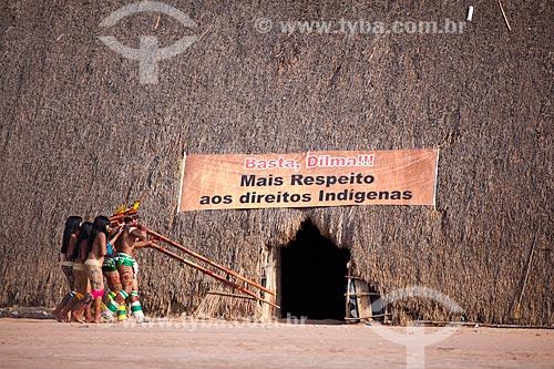 Índios Yawalapiti tocando a flauta Uruá no ritual do Kuarup com uma faixa de protesto em que se lê: