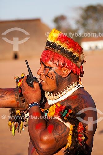 Índios Yawalapiti com tunacape (cocar), pintura e adorno corporal utilizando colar feito de presa (dente) de animal e aparelho portátil de rádio,tipo celular, como meio de comunicação à distância durante o Kuarup - cerimônia deste ano em homenagem ao antropólogo Darcy Ribeiro - Imagem licenciada (Released 94) - ACRÉSCIMO DE 100% SOBRE O VALOR DE TABELA  - Gaúcha do Norte - Mato Grosso - Brasil