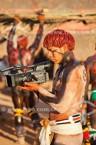 Índio com pintura e adorno corporal com filmadora digital Panasonic durante o ritual do Kuarup - cerimônia deste ano em homenagem ao antropólogo Darcy Ribeiro - Imagem licenciada (Released 94) - ACRÉSCIMO DE 100% SOBRE O VALOR DE TABELA  - Gaúcha do Norte - Mato Grosso - Brasil