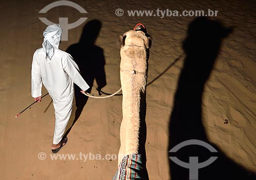 Assunto: Homem com camelo no deserto em Sharjah / Local: Sharjah - Emirados Árabes Unidos - Ásia / Data: 10/2012
