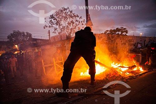 Assunto: Policial apagando uma fogueira durante a ocupação no conjunto de favelas do Jacarezinho e Manguinhos para implantação da Unidade de Policia Pacificadora (UPP) / Local: Rio de Janeiro (RJ) - Brasil / Data: 10/2012