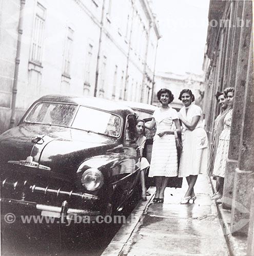 Jovens mulheres posam para fotografia junto ao automóvel Chevrolet Styleline De Luxe na Rua Leandro Martins com Colégio Pedro II à esquerda - Câmera Rolleiflex - (uso editorial)  - Rio de Janeiro - Rio de Janeiro - Brasil