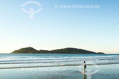 Assunto: Garoto andando na água na Praia do Campeche ao amanhecer com a Ilha do Campeche ao fundo / Local: Florianópolis - Santa Catarina (SC) - Brasil / Data: 06/2013