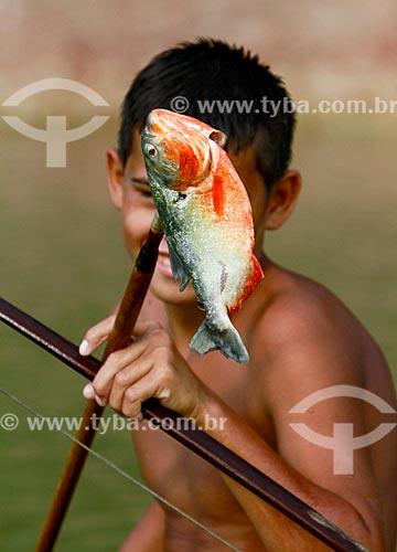 Assunto: Menino segurando uma piranha no Lago do Ariaú / Local: Iranduba - Amazonas (AM) - Brasil / Data: 11/2013