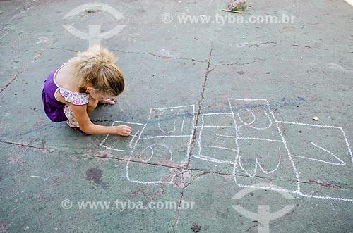 Assunto: Menina desenhando amarelinha em frente ao Mercado do Porto / Local: Mato Grosso (MT) - Brasil / Data: 07/2013