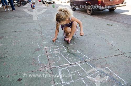 Assunto: Menina desenhando amarelinha em frente ao Mercado do Porto / Local: Cuiabá - Mato Grosso (MT) - Brasil / Data: 07/2013