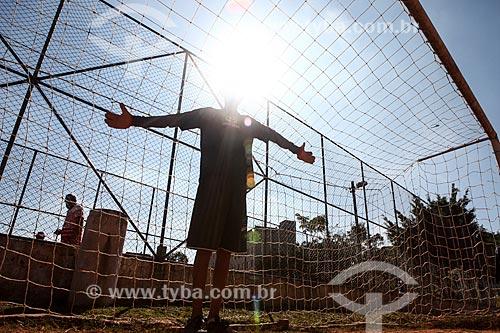 Assunto: Menino jogando futebol em campo de terra próximo à Arena Corinthians / Local: Itaquera - São Paulo (SP) - Brasil / Data: 06/2014