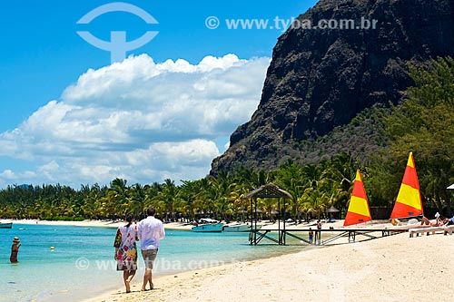 Assunto: Casal caminhando na praia com a montanha na Península Le Morne Brabant ao fundo / Local: Distrito de Rivière Noire - Maurício - África / Data: 11/2012