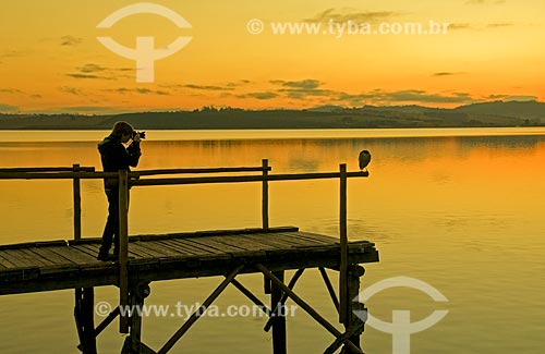 Jovem fotografando pássaro no píer da Represa de Furnas durante o nascer do sol  - Boa Esperança - Minas Gerais (MG) - Brasil