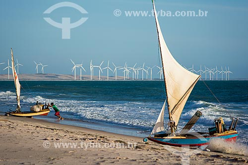 Pescador em jangada na Praia de Canoa Quebrada com o Parque Eólico Canoa Quebrada ao fundo  - Aracati - Ceará (CE) - Brasil