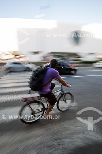 Ciclista passando sobre a faixa de pedestre e ao fundo Biblioteca Municipal Governador Leonel de Moura Brizola - Centro Cultural Oscar Niemeyer  - Duque de Caxias - Rio de Janeiro (RJ) - Brasil