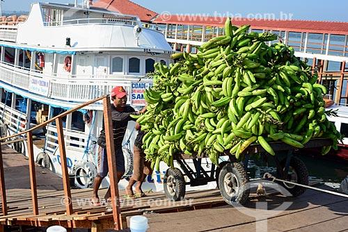 Homens descarregando carrinho de mão com bananas em porto às margens do Rio Tapajós  - Itaituba - Pará (PA) - Brasil
