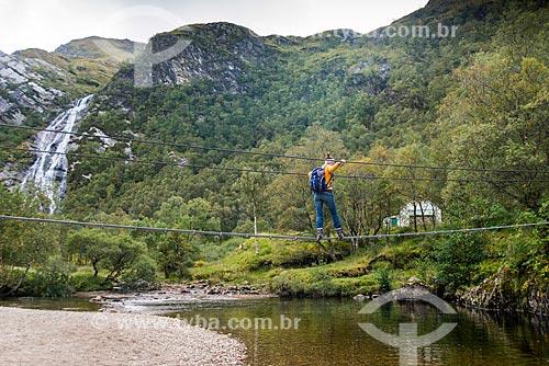 Turista atravessando ponte sobre o rio na trilha em Fort William - próximo à região de Glen coe  - Fort William - Highland - Escócia