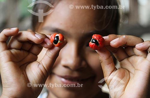 Criança ribeirinha segurando os frutos do Guaraná (Paullinia cupana) - assemelhando-se com os olhos  - Maués - Amazonas (AM) - Brasil