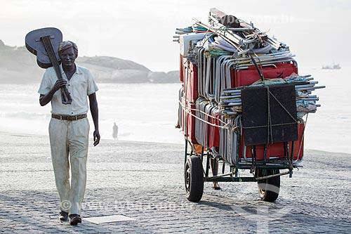Burro-sem-rabo carregando cadeiras de praia próximo à estátua do maestro Tom Jobim no calçadão da Praia do Arpoador  - Rio de Janeiro - Rio de Janeiro (RJ) - Brasil