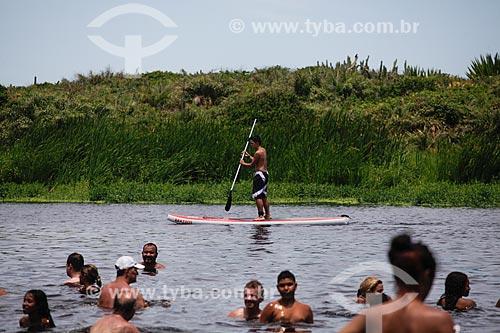 Praticante de stand up paddle e banhistas na Lagoa do Iriri - também conhecida como Lagoa da Coca-Cola  - Rio das Ostras - Rio de Janeiro (RJ) - Brasil