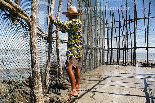 Homem consertando cerca na orla da Ilha de Maiandeua  - Maracanã - Pará (PA) - Brasil