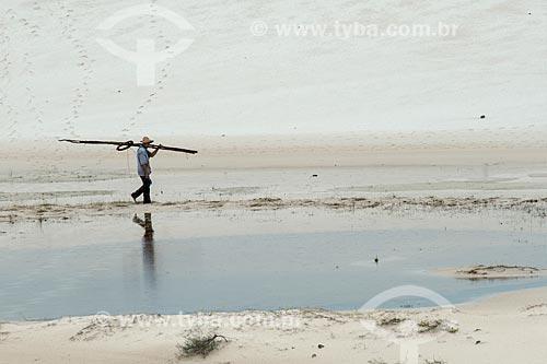 Homem caminhando às margens de pequena lagoa no Parque Nacional dos Lençóis Maranhenses  - Barreirinhas - Maranhão (MA) - Brasil