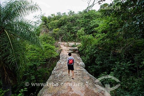 Turista atravessando o Geossítio Ponte de Pedra - aproximadamente com 96 milhões de anos (Período Cretáceo) - no Geoparque Araripe  - Nova Olinda - Ceará (CE) - Brasil