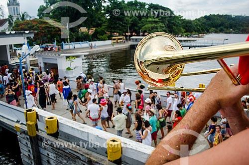 Pessoa tocando trombone e foliões desembarcando na Ilha de Paquetá para bloco de carnaval  - Rio de Janeiro - Rio de Janeiro (RJ) - Brasil