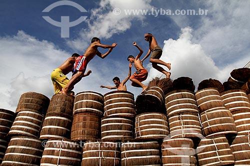 Jovens brincando em meio ao carregamento de Piaçava (Attalea funifera) no porto da cidade de Barcelos  - Barcelos - Amazonas (AM) - Brasil