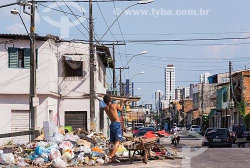 Menino jogando lixo e entulho em rua do bairro Sacramenta  - Belém - Pará (PA) - Brasil
