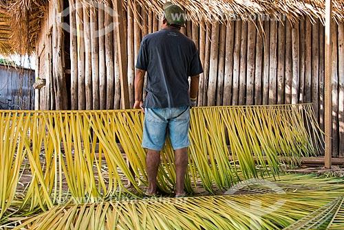 Homem construindo telhado de quiosque com a palha da curuá-pixuna (Orbignya Pixuna)  - Santarém - Pará (PA) - Brasil