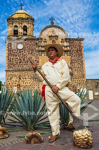 Cortador de agave-azul (Agave tequilana) - matéria-prima para a produção da tequila - com a Parroquia Santiago Apóstol (Paróquia de Santiago Apóstolo) ao fundo  - Tequila - Jalisco - México