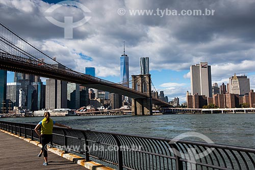 Mulher se exercitando às margens do Rio East com a Ponte do Brooklyn ao fundo  - Cidade de Nova Iorque - Nova Iorque - Estados Unidos