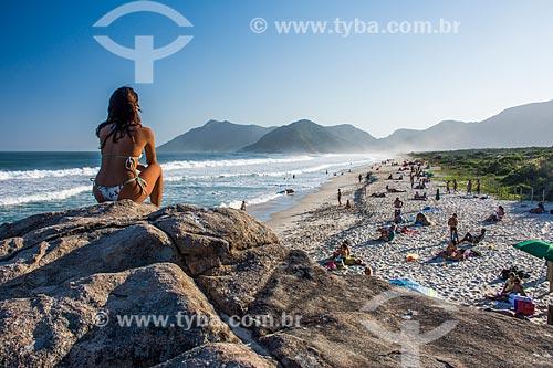 Mulher observando o pôr do sol das pedras na orla da Praia de Grumari  - Rio de Janeiro - Rio de Janeiro (RJ) - Brasil
