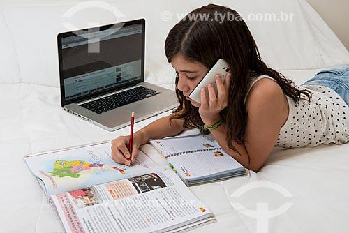 Menina estudando com livro, computador e telefone celular  - Rio de Janeiro - Rio de Janeiro (RJ) - Brasil