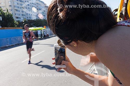 Mulher fotografando atleta durante corrida em competição de triatlo - evento-teste para Jogos Olímpicos - Rio 2016 - na orla da Praia de Copacabana  - Rio de Janeiro - Rio de Janeiro (RJ) - Brasil