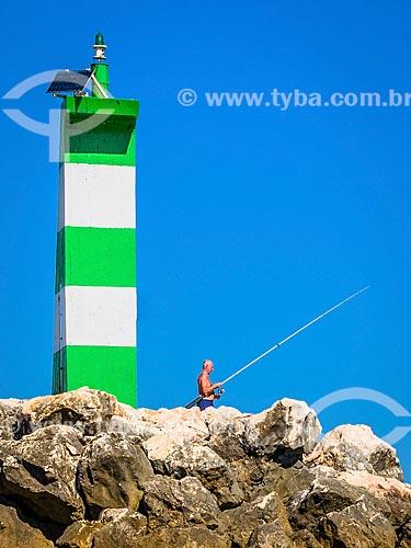 Pescador em rocha na orla do concelho de Lagos  - Concelho de Lagos - Distrito de Faro - Portugal