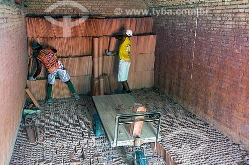 Trabalhadores retirando telhas do forno de olaria  - Nazária - Piauí (PI) - Brasil