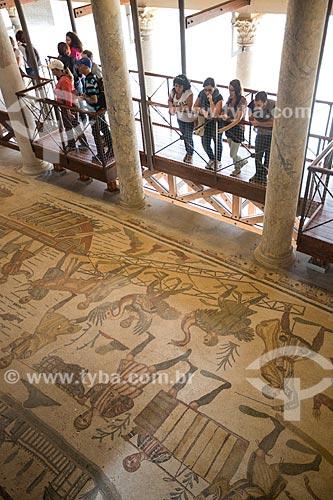 Turistas observando o mosaico conhecido como a Grande Caçada na Villa Romana del Casale - antiga palácio construído no século IV  - Piazza Armerina - Província de Enna - Itália