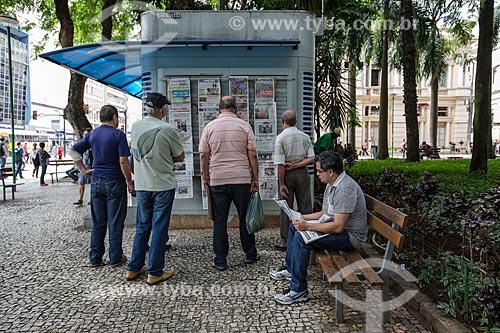 Homens lendo jornais expostos em banca de jornal no Parque Halfeld  - Juiz de Fora - Minas Gerais (MG) - Brasil