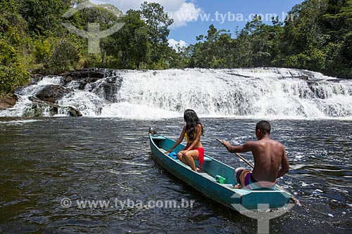 Casal em canoa no Rio Maraú com a Cachoeira do Tremembé ao fundo  - Maraú - Bahia (BA) - Brasil