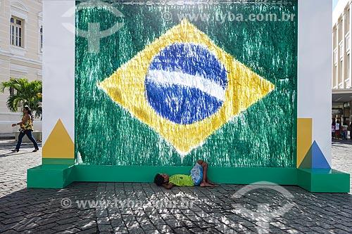 Menino de rua dormindo em frente à grafite da Bandeira do Brasil no Pelourinho  - Salvador - Bahia (BA) - Brasil