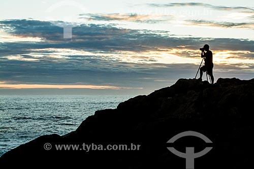Homem fotografando o costão da Ilha das Campanhas na Praia da Armação do Pântano do Sul durante o amanhecer  - Florianópolis - Santa Catarina (SC) - Brasil