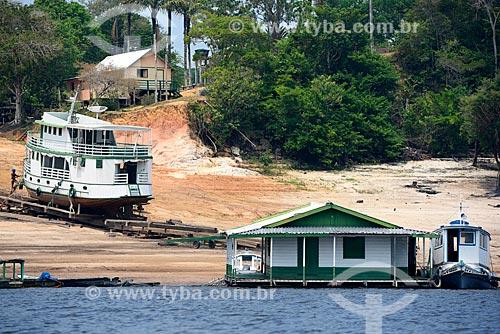 Barco sendo reparado na margem do Rio Negro  - Novo Airão - Amazonas (AM) - Brasil