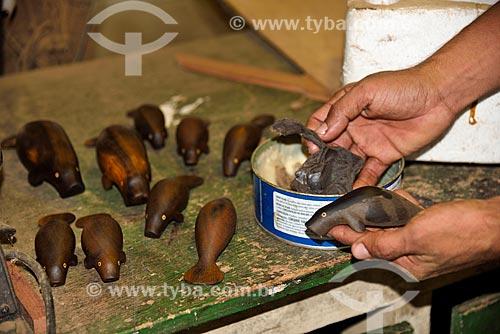 Artesão aplicando cera em peça de madeira feita na Associação de Produtores Nov Arte - apoiada pela Fundação Almerinda Malaquias  - Novo Airão - Amazonas (AM) - Brasil