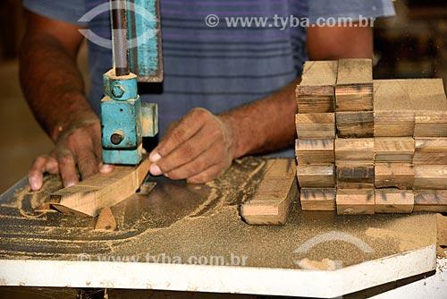 Artesão cortando peças de madeira para entalhe dos artesanatos na Associação de Produtores Nov Arte - apoiada pela Fundação Almerinda Malaquias  - Novo Airão - Amazonas (AM) - Brasil