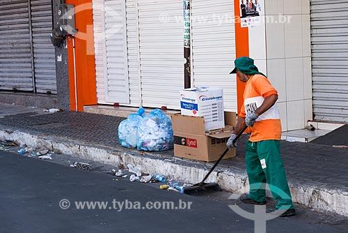 Homem varrendo lixo e sujeira deixados na via pública após o fechamento do comércio  - Juazeiro do Norte - Ceará (CE) - Brasil