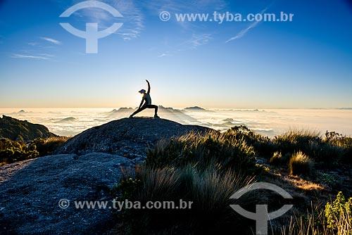 Mulher praticando Yoga - movimento virabhadrasana (guerreiro) - na trilha da Pedra do Sino no Parque Nacional da Serra dos Órgãos  - Teresópolis - Rio de Janeiro (RJ) - Brasil